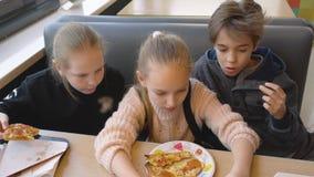 Equipo del adolescente que come la pizza en la opinión superior del restaurante italiano de los alimentos de preparación rápida almacen de metraje de vídeo