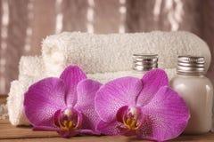 Equipo del balneario con las lociones para la piel, las flores de la orquídea y las toallas blancas Fotos de archivo