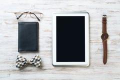 Equipo del caballero de los vidrios de reloj de la tableta corbata de lazo y cuaderno en la tabla de madera Imagen de archivo libre de regalías