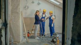 Equipo del emplazamiento de la obra o arquitecto y constructor o trabajador con los cascos que controlan o que tienen discusión d almacen de metraje de vídeo