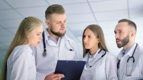 Equipo del especialista médico que habla con uno a al ángulo bajo del hospital almacen de video