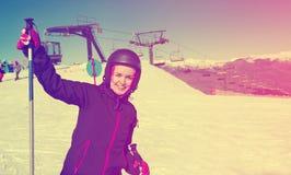 Equipo del esquí de la mujer que lleva y esquí en montañas que nievan Imágenes de archivo libres de regalías