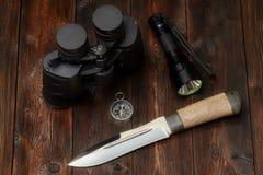 Equipo del explorador o del cazador en un fondo de madera fotografía de archivo