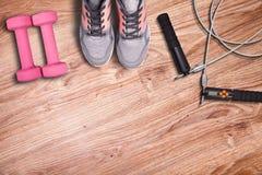 Equipo del gimnasio en el piso de madera Zapatos y comba del funcionamiento del deporte Imagenes de archivo
