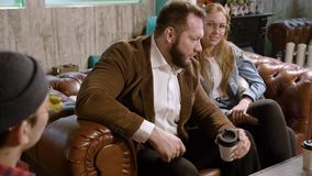 Equipo del grupo de la gente joven que sostiene las tazas de café y que discute algo con sonrisa mientras que se sienta en el sof almacen de video