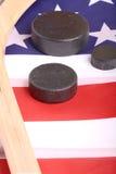 Equipo del hockey incluyendo un palillo y duende malicioso en una bandera americana para deducir un deporte americano patriótico Foto de archivo libre de regalías