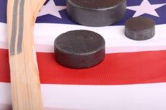 Equipo del hockey incluyendo un palillo y duende malicioso en una bandera americana para deducir un deporte americano patriótico Fotografía de archivo libre de regalías