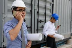 Equipo del ingeniero usando smartphone en el emplazamiento de la obra Imagen de archivo libre de regalías