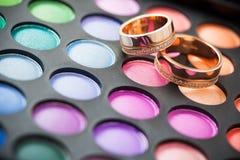 Equipo del maquillaje para los ojos y los anillos de bodas fotos de archivo libres de regalías