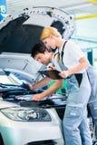 Equipo del mecánico que trabaja en taller del coche Foto de archivo libre de regalías