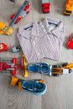 Equipo del muchacho cerca del juguete del coche La camisa rayada y el barco azul calza los coches rojos amarillos Visión superior foto de archivo