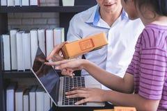 Equipo del negocio casero que comprueba la acción en su negocio casero en línea imagen de archivo