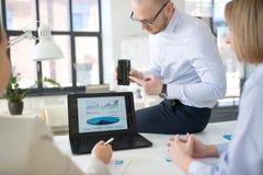 Equipo del negocio con el funcionamiento del smartphone en la oficina foto de archivo libre de regalías