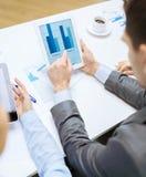 Equipo del negocio con el gráfico en la pantalla de la PC de la tableta Fotografía de archivo libre de regalías
