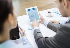 Equipo del negocio con el gráfico en la pantalla de la PC de la tableta foto de archivo