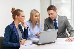 Equipo del negocio con el ordenador portátil que tiene discusión Imagen de archivo