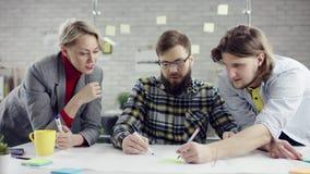 Equipo del negocio de gente útil joven que disfruta del trabajo junto, grupo de los millennials que habla divirtiéndose en oficin almacen de video