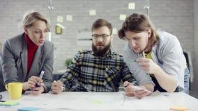 Equipo del negocio de gente seria joven que disfruta del trabajo junto, grupo de los millennials que habla divirtiéndose en ofici almacen de metraje de vídeo