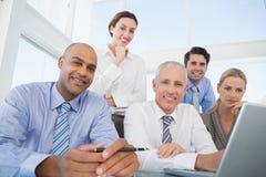 Equipo del negocio durante la reunión que sonríe en la cámara Foto de archivo libre de regalías