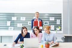 Equipo del negocio en un interior brillante moderno de la oficina en el trabajo sobre un ordenador portátil imagen de archivo