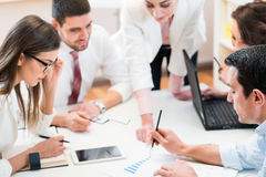 Equipo del negocio que analiza datos y que discute estrategia Foto de archivo libre de regalías