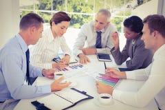 Equipo del negocio que analiza gráficos de la carta de barra Imagen de archivo