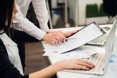 Equipo del negocio que analiza gráficos de la renta con los ordenadores portátiles modernos Ciérrese encima de concepto del análi imagen de archivo