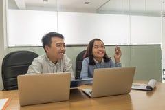 Equipo del negocio que comparte ideas y que las discute el uno al otro en sala de reunión imagenes de archivo