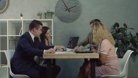Equipo del negocio que discute cartas y gráficos en oficina almacen de metraje de vídeo