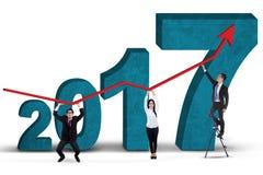 Equipo del negocio que lleva a cabo el gráfico con los números 2017 Imagen de archivo libre de regalías