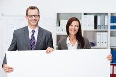 Equipo del negocio que lleva a cabo una muestra blanca en blanco Imagenes de archivo