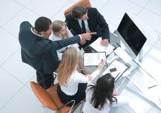 Equipo del negocio que mira documentos en la oficina con el encargado, foto de archivo libre de regalías
