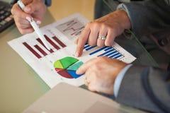 Equipo del negocio que pasa datos y gráficos Imagen de archivo libre de regalías
