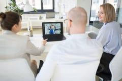 Equipo del negocio que tiene videoconferencia en la oficina imagenes de archivo