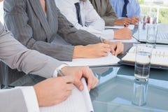 Equipo del negocio que toma notas durante conferencia fotografía de archivo