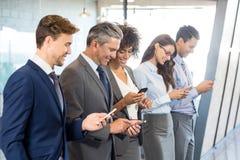 Equipo del negocio usando su teléfono móvil Fotografía de archivo libre de regalías