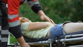 Equipo del paramédico que lleva a la hembra inconsciente en el ensanchador, primeros auxilios del profesional almacen de video