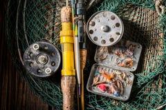 Equipo del pescador con las moscas y las barras de la pesca Imagen de archivo