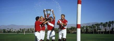Equipo del polo que celebra con el trofeo en campo Imagen de archivo libre de regalías
