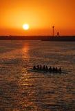 Equipo del Rowing de la puesta del sol Foto de archivo