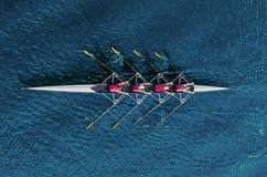 Equipo del rowing del ` s de las mujeres en el agua azul fotografía de archivo