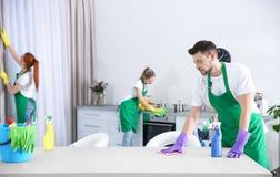 Equipo del servicio de la limpieza que trabaja en cocina Foto de archivo libre de regalías