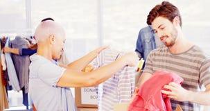 Equipo ejecutivo creativo feliz que clasifica la ropa en caja de la donación