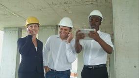 Equipo ejecutivo en emplazamiento de la obra que discute proyecto, usando la tableta, teniendo llamadas de teléfono con smartphon almacen de metraje de vídeo