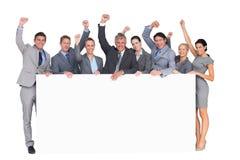 Equipo emocionado del negocio que sostiene el cartel Fotografía de archivo