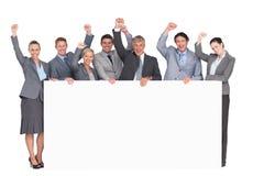 Equipo emocionado del negocio que sostiene el cartel Fotografía de archivo libre de regalías