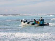 Equipo en el bote pequeño que vuelve a Arniston a partir de un día de pesca Fotografía de archivo libre de regalías