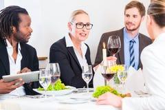 Equipo en la reunión de almuerzo de negocios en restaurante Imagenes de archivo