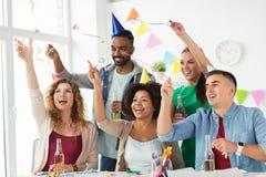 Equipo feliz con confeti en la fiesta de cumpleaños de la oficina Imagen de archivo libre de regalías