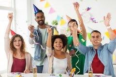 Equipo feliz con confeti en la fiesta de cumpleaños de la oficina Imágenes de archivo libres de regalías